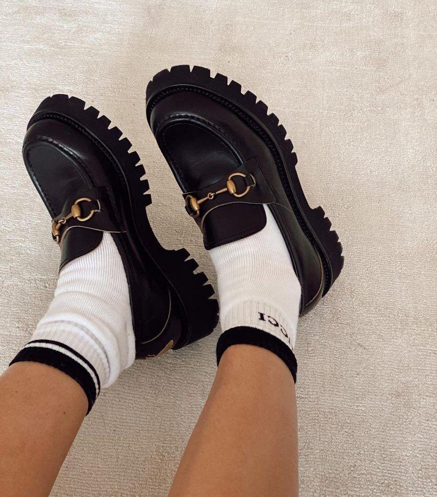 一雙腳穿著gucci樂福鞋搭配襪子的腳