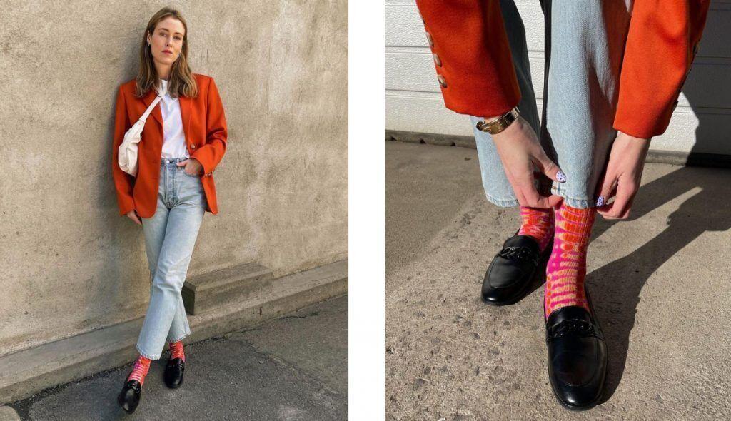 西裝外套和襪子都是亮眼的橘紅色的女士靠在牆上,搭配黑色的樂福鞋